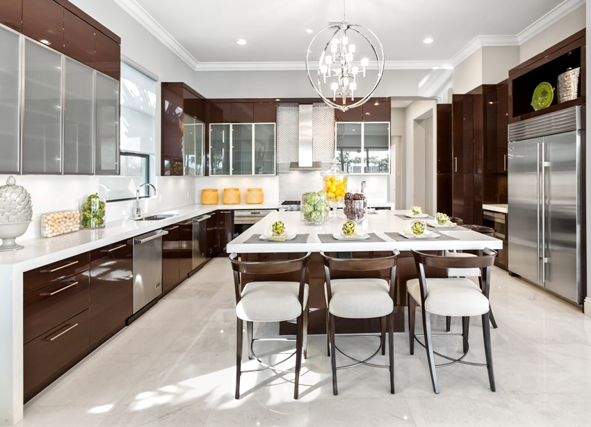 Classy kitchen interior with crema marfil marble floor center island with chairs and hanged ceiling lights
