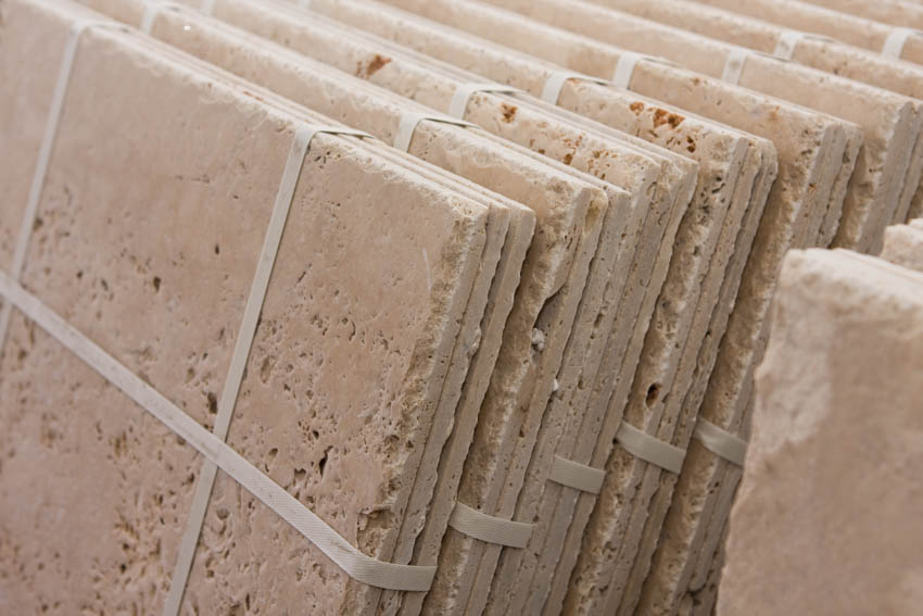 Close up of stack of travertine tiles with holes