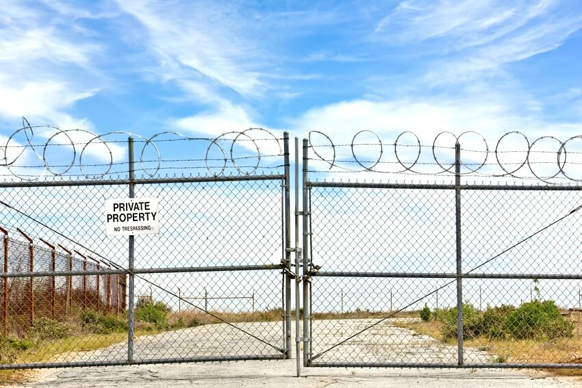 Closed gate with a chain and several padlocks and a private property sign hanging on a metal fence