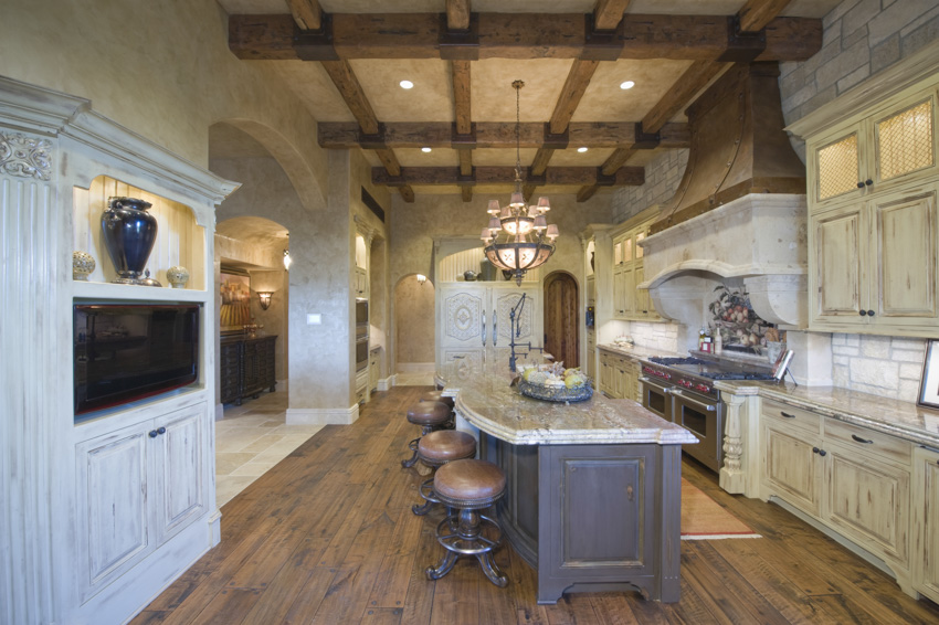 Coffered ceiling center island wood floor white cabinets tuscan kitchen