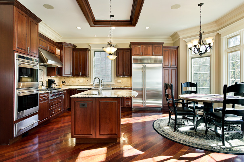 Combined kitchen and dining with cherry wood floor and cabinets