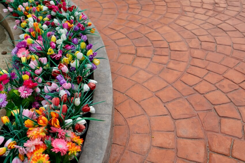 Concrete paver look with colorful flowers on the side