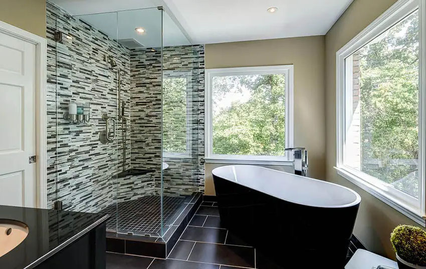 Bathroom with frameless shower doors and black tiles and picture window