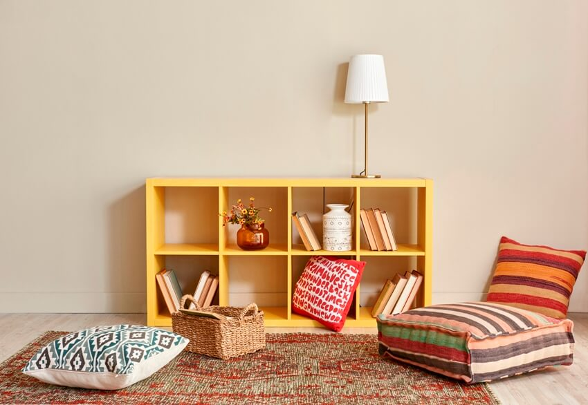 A cozy home decoration young room interior style yellow cube bookshelf red seat and cushion