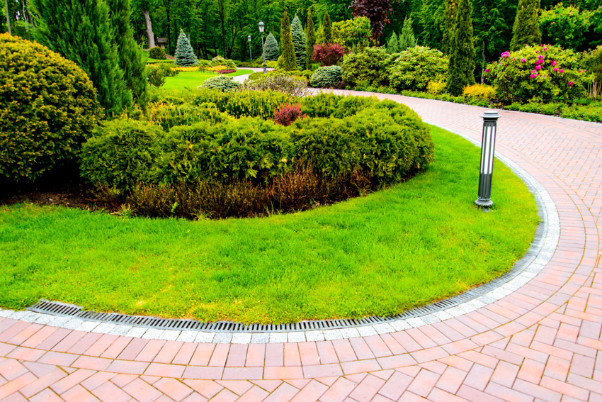 Curving brick walkway landscaped area light mounted on path