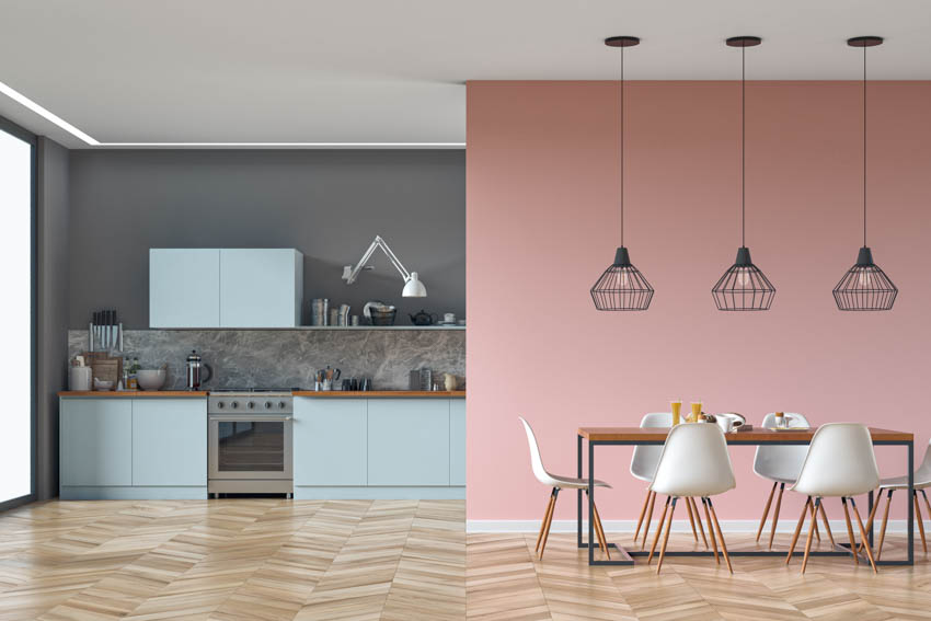Dark kitchen area contrasted by pastel pink dining room pattern wood floor hanging light