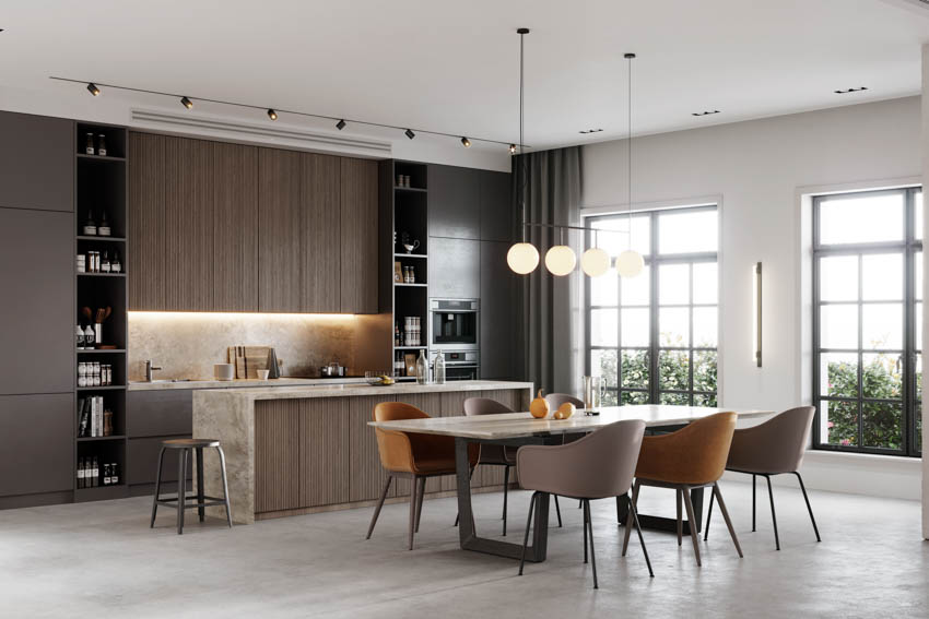 Dark kitchen with brown cabinets chairs hanging lights framed windows