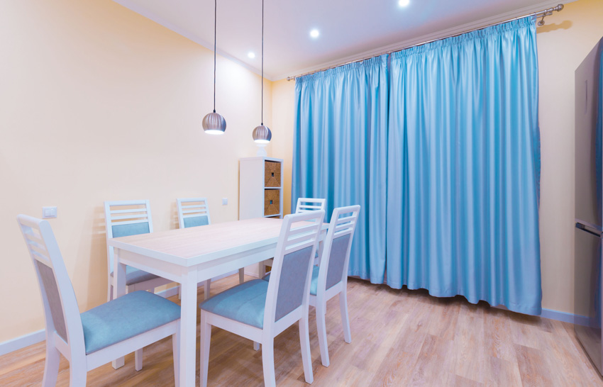 Dining room with yellow wall hanging light teal curtain