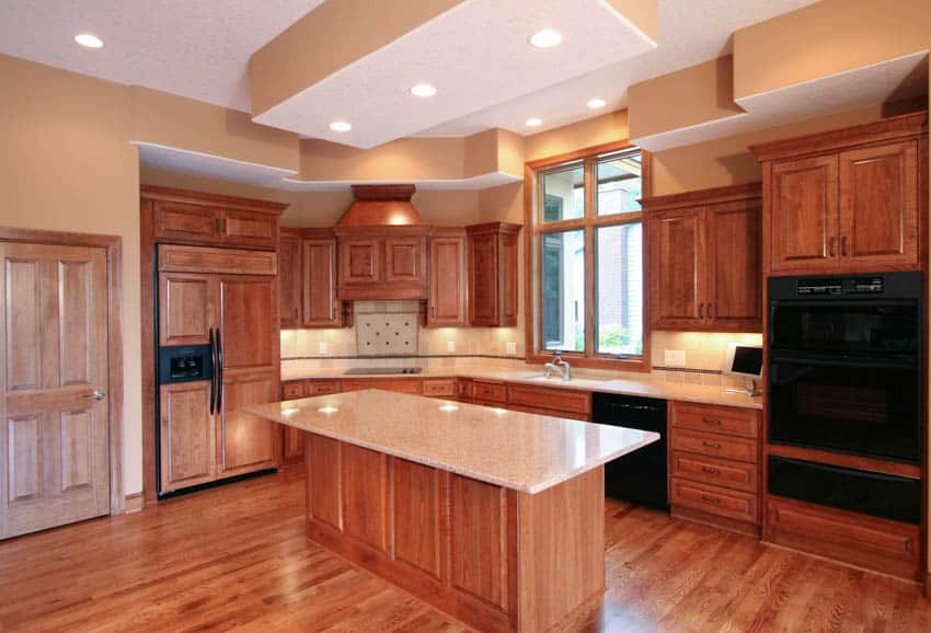 Empty kitchen space with wood cabinets center island countertops