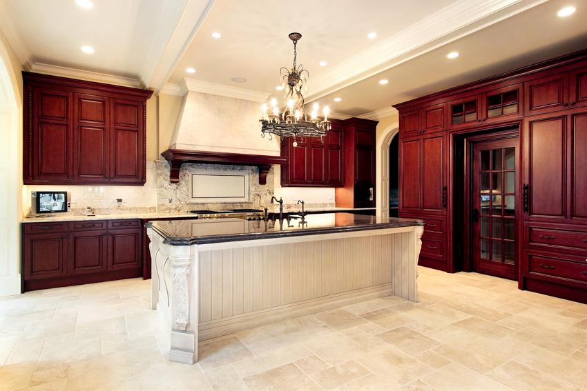 Empty kitchen with tile flooring center island cherry wood cabinets chandelier