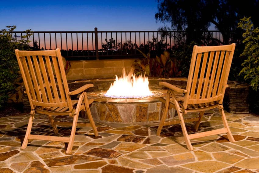 Fire pit burning at night lounge chairs patio tiles