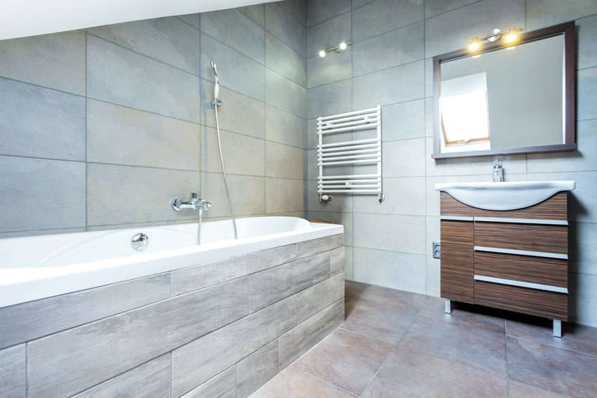 A fully tiled bathroom interior with bath and wooden shelf