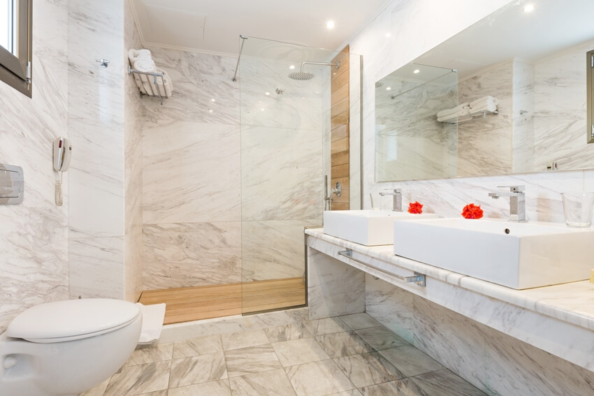 Fully tiled bathroom interior with mirror bidet and shower
