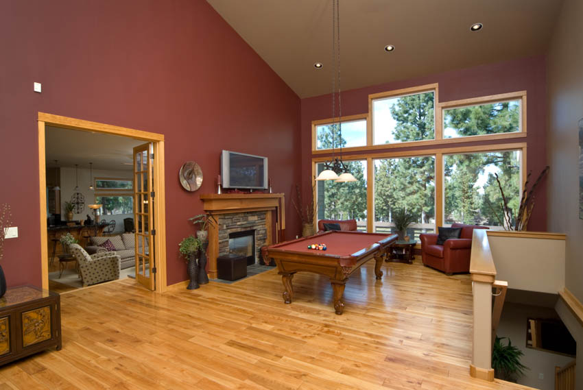Game room with wood floor red wall billiards table