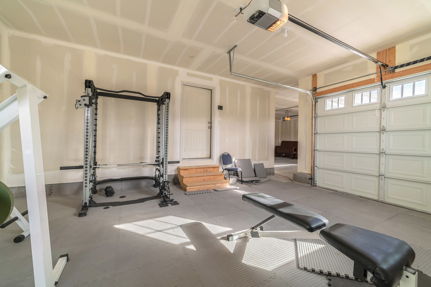 Garage interior with various fitness equipment and rubber flooring