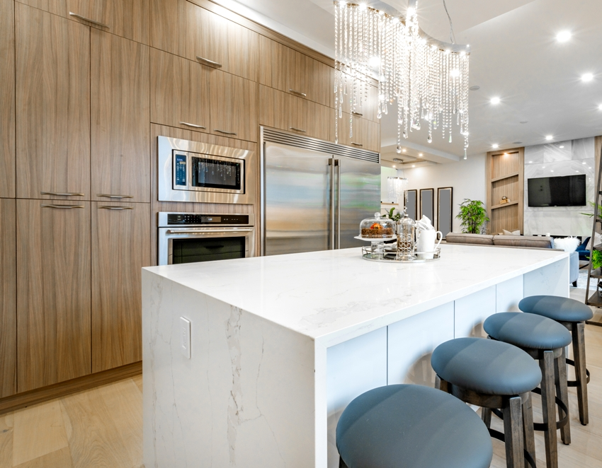 Gorgeous kitchen with wooden cabinets and white kitchen island with chairs and marble countertop