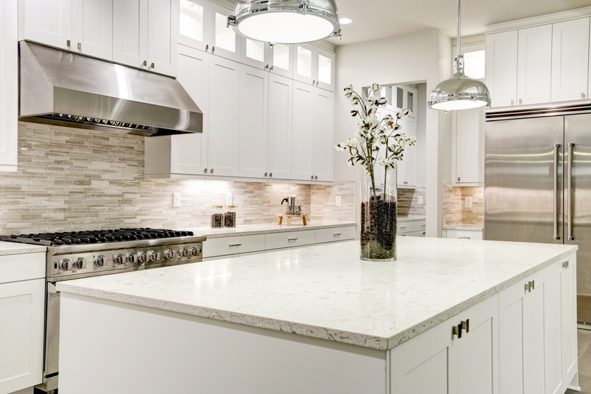A gourmet kitchen features white shaker double stacked cabinets with marble countertops and white kitchen island