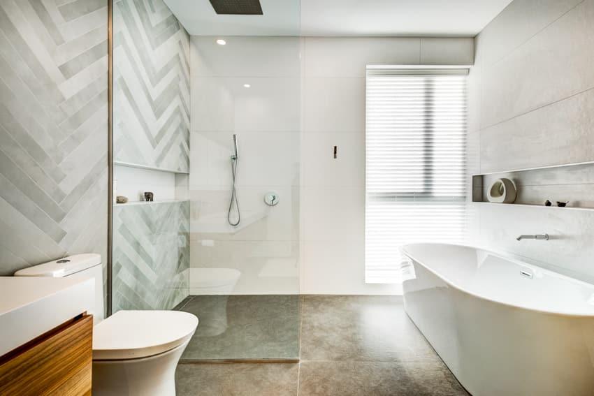 Gray bathroom with bathtub tile flooring glass shower area toilet