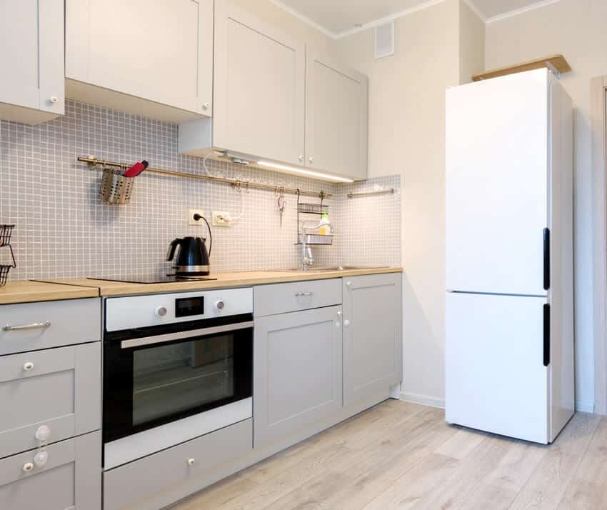 Gray interior of a small cozy kitchen with white appliances