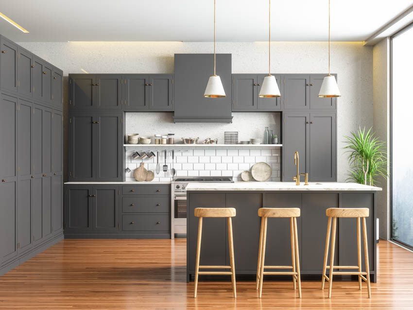 Gray kitchen with stained wood floor stools center island for dining indoor plant large window