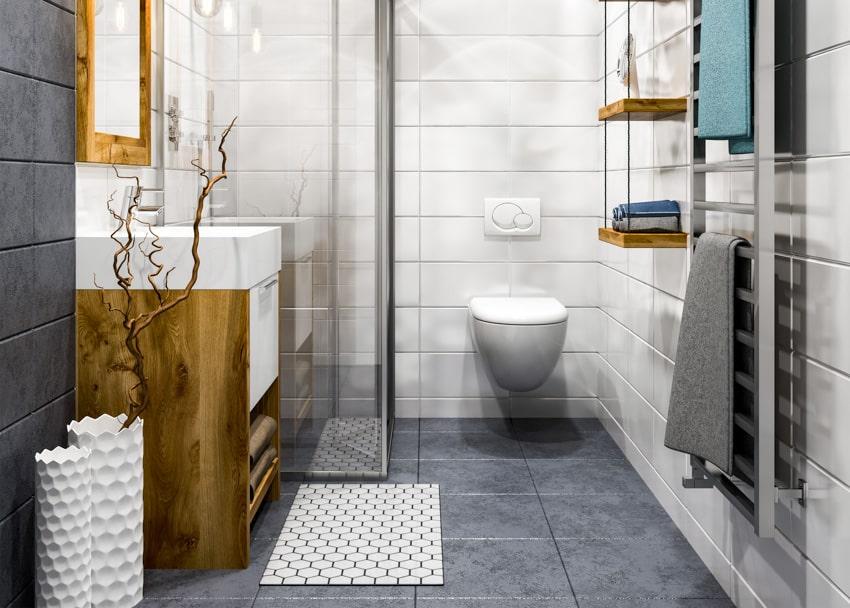 Gray tile floor glass shower area toilet white wall