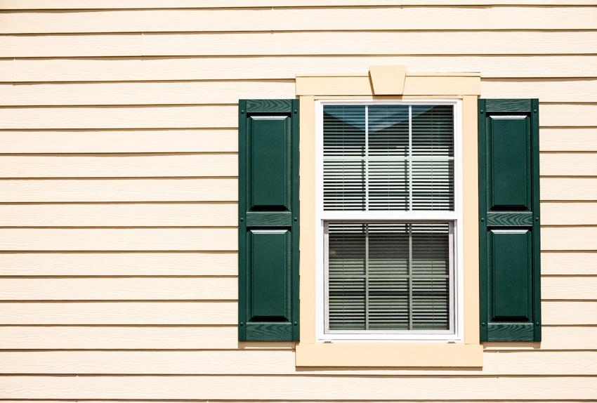 Green raised panel shutters glass windows white exterior siding