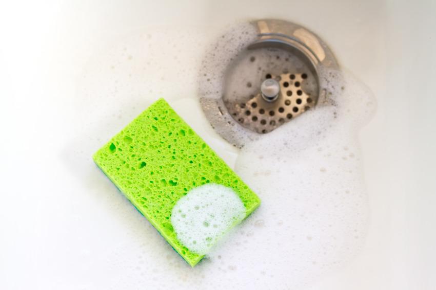 Green sponge in soapy kitchen sink