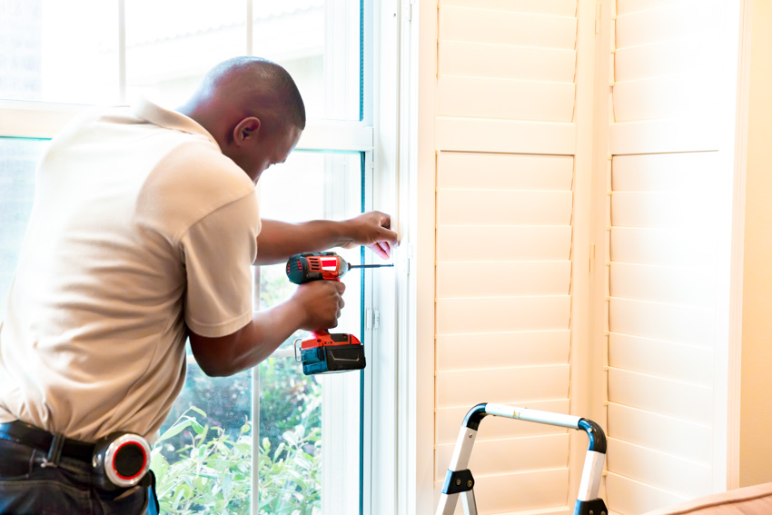 Handyman installing interior shutters