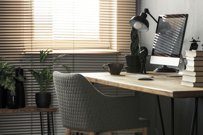 Home office interior with chair wooden desk and aluminum blinds