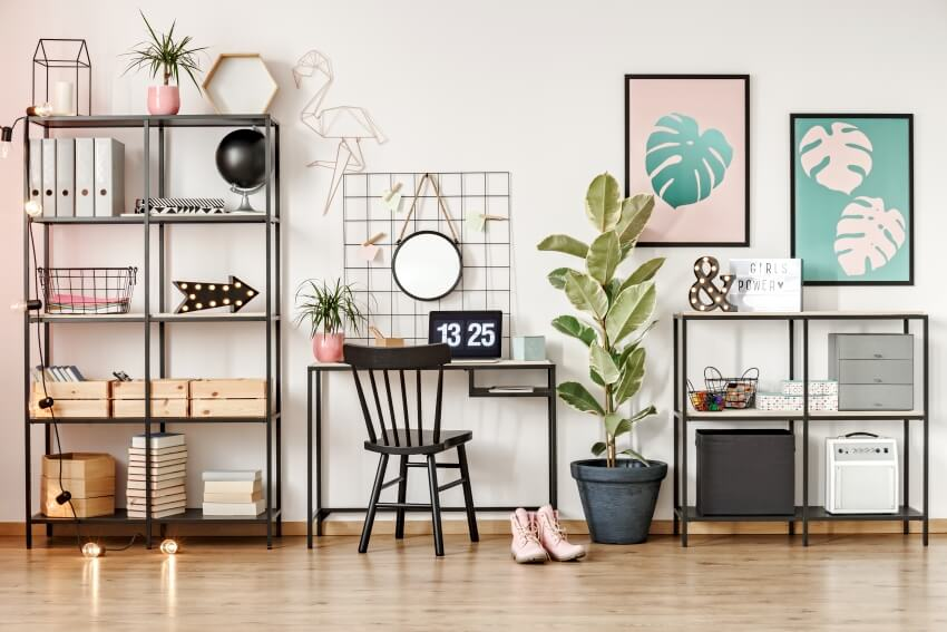Home office interior with metal bookshelves a black chair at desk with laptop with leaves posters and ficus