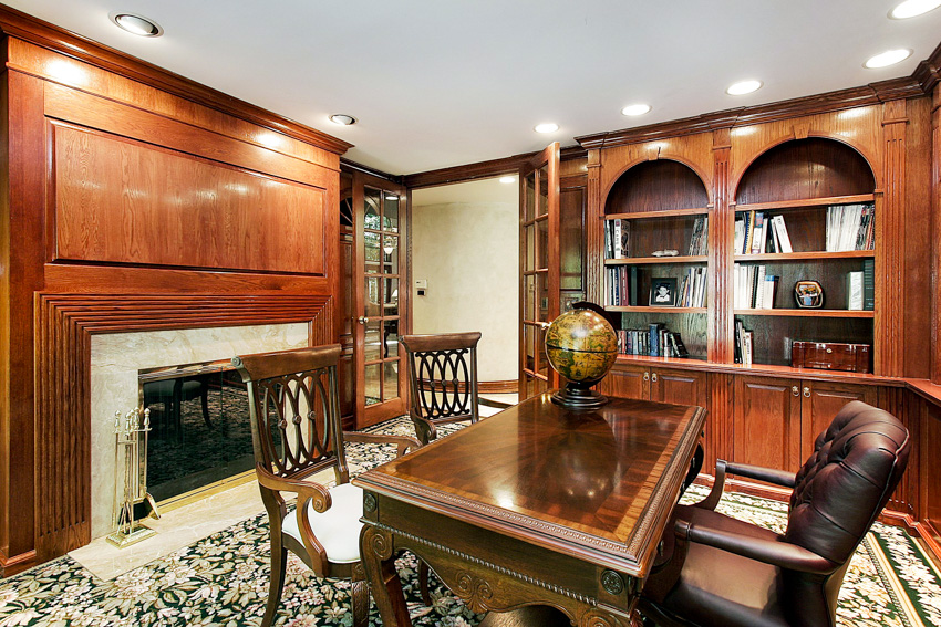 Home office with cherry wood desk cabinets wall and fireplace