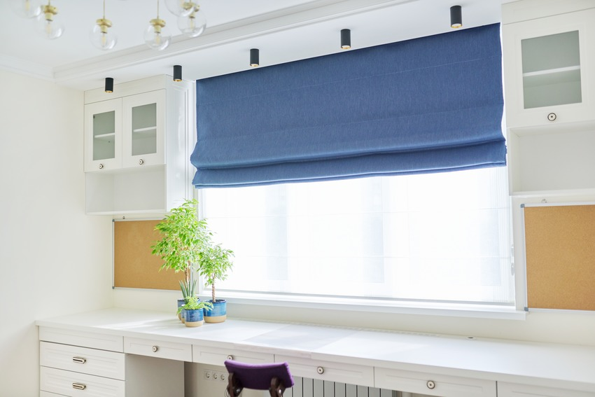 Home workplace interior with blue roman blinds