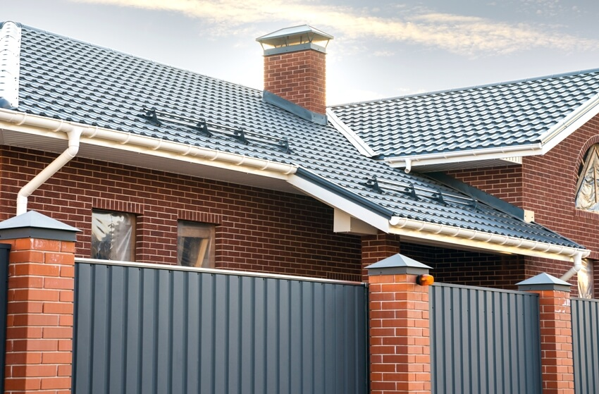 House exterior with a gutter system on a metal roof a brick chimney pipe and automatic metal gates
