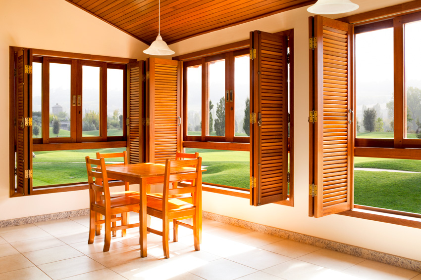 House interior shutters made of wood small table chairs wooden flooring hanging light