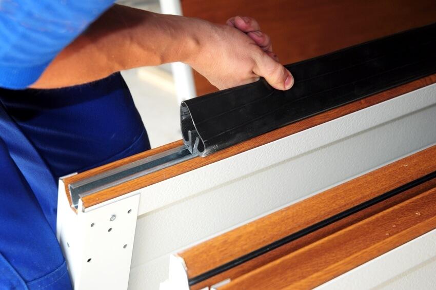 Man installing garage door weatherproofing garage door seal