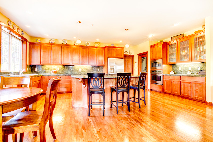 Kitchen and dining room combined with cherry wood floor and cabinets