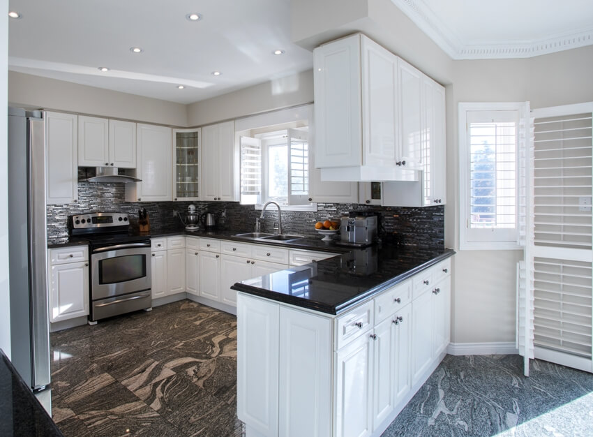Kitchen area with white cabinets stainless steel appliances and black marble floor tiles