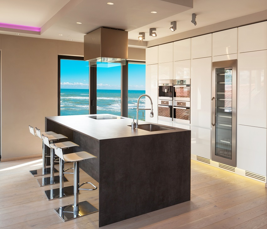 Kitchen interior with beige walls white double stacked cabinets and island with chairs