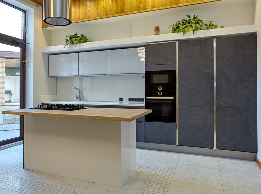 Kitchen interior with handleless cabinets and kitchen island with stove