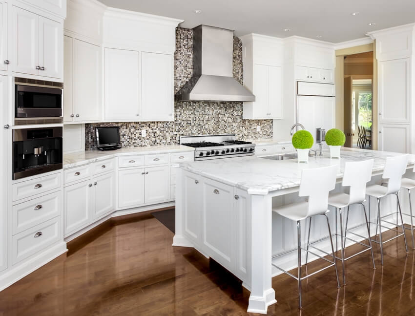 Kitchen interior with island sink cabinets oven range backsplash and hardwood floors