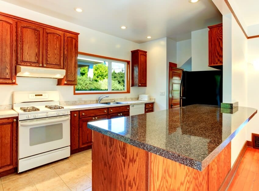 Kitchen interior with tile floor dark wooden cabinets with granite tops and white appliances