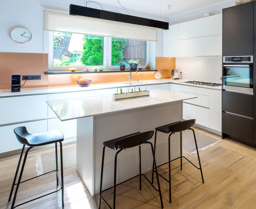 Kitchen interior with wooden floors white j pull kitchen cabinets center island and chairs