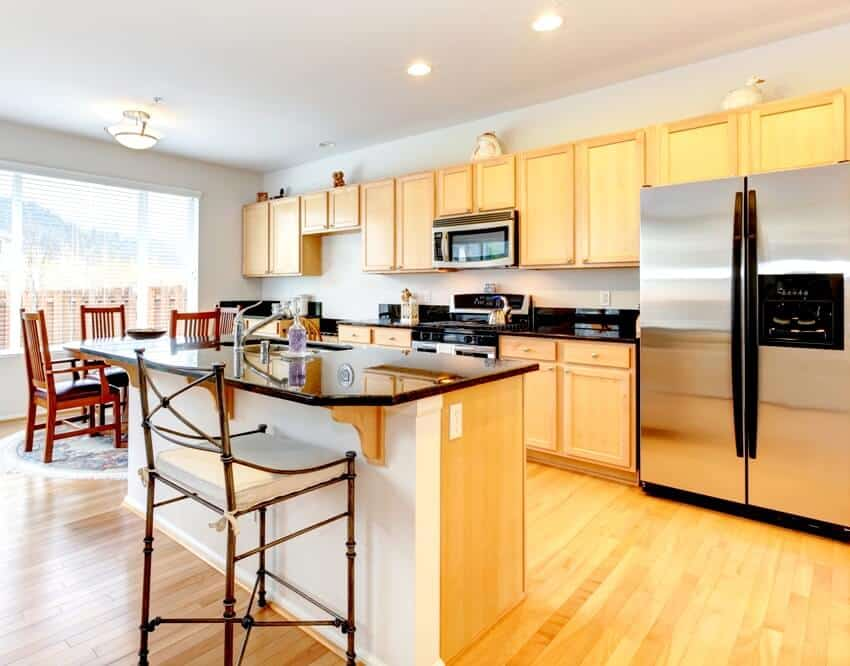A kitchen iterior with maple cabinets center island and appliances