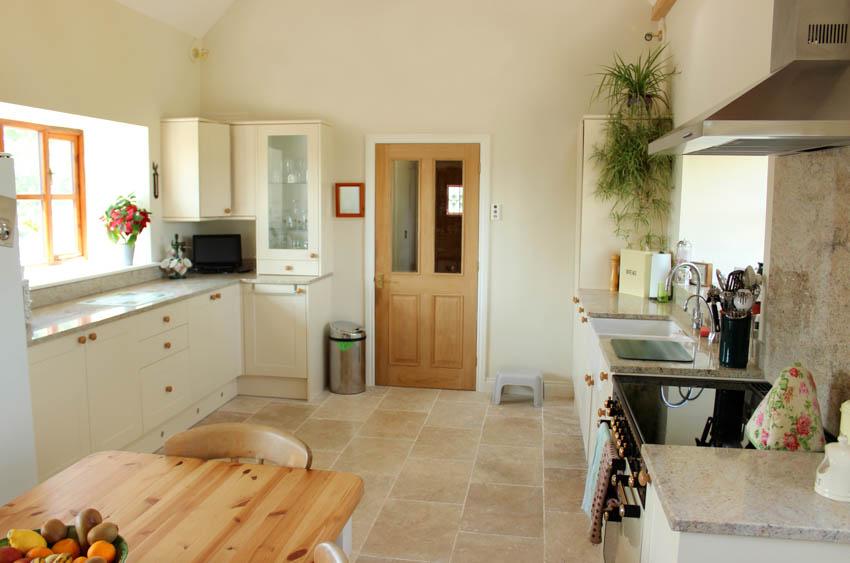 Kitchen travertine tile floor with hood sink wood table door window