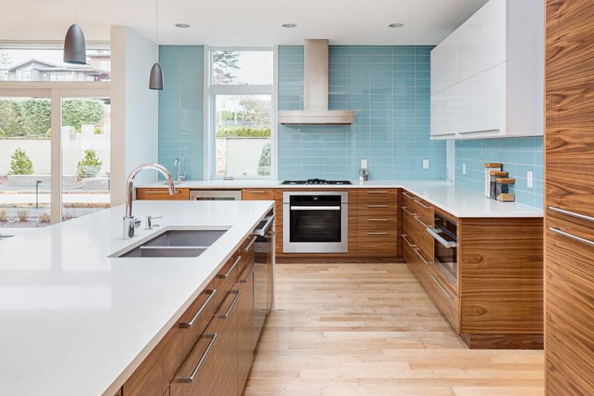 Kitchen with light blue backsplash wood cabinets drawers white countertop