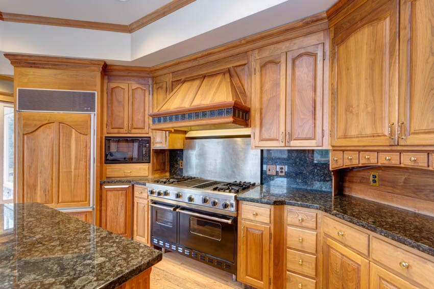 Kitchen with maple cabinets drawers oven hood countertop