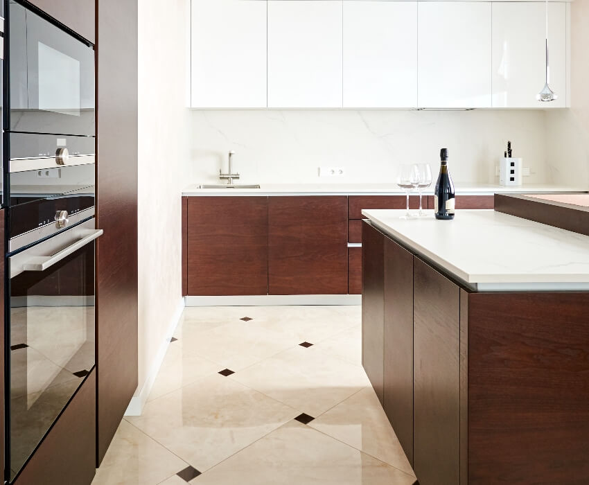 Kitchen with wooden cabinets built in oven and repeating marble tile pattern