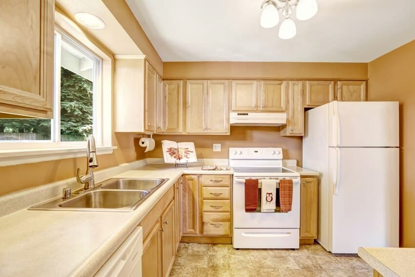 Kitchen with wooden cabinets in light tones with white appliances