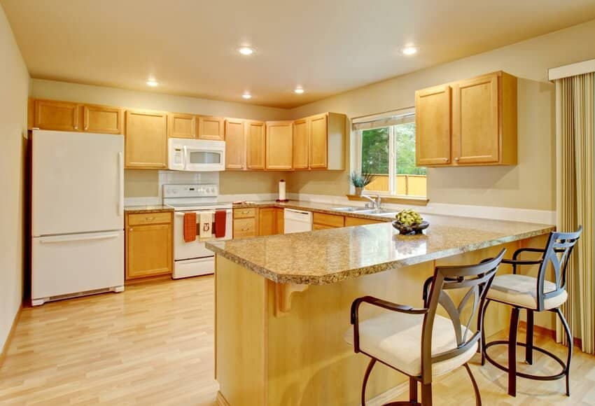 Kitchen with yellow lighting white appliances and maple cabinets