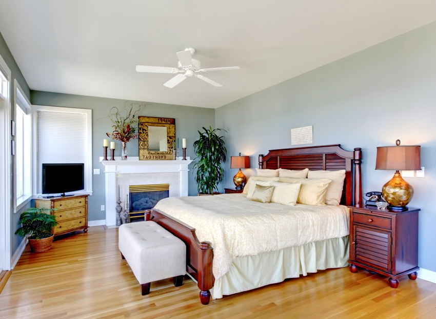 Large bedroom with fireplace cherry wood furniture and green walls